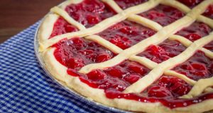 Fresh Cherry Pie. Hot cherry pie fresh from the oven with lattice on a blue and white gingham background.